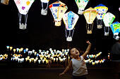 Taitung, China's Taiwan. 28th Sep, 2014. A child is attracted by colorful lanterns at Tiehua Music Village in Taitung, southeast China's Taiwan, late Sept. 28, 2014. Artists and locals made and painted some 3,000 hot-air-balloon-shaped lanterns this summer to decorate the nearby meadow of the village, echoing the annual balloon fiesta of the city. © Wang Qingqin/Xinhua/Alamy Live News - Stock Image - E81EPF