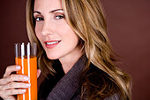 A mid adult woman holding a glass of fruit/carrot juice - Stock Image - BH67M7