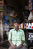 Man sitting in front of shop - Stock Image - CFAH02