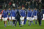 Schalke's players leave the field in disappointment after a Bundesliga game of FC Schalke 04 versus Eintracht Frankfurt at the Commerzbank Arena in Frankfurt, Germany, 23 October 2010. Frankfurt's coach Michael Skibbe watches them. Photo: Alfred Harder - Stock Image - D527YX