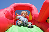 Child on inflatable bouncy castle slide - Stock Image - CTG40P