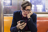 Businessman using cell phone on subway - Stock Image - D4K9D8
