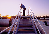 Engineer on a walkie talkie radio at sunset at a waste water treatment plant, Houston, Texas, USA - Stock Image - C12C0G
