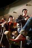 Low angle view of friends sitting at bar drinking and hanging out - Stock Image - B720BK