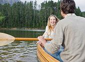 Couple rowing canoe on lake - Stock Image - BCA197