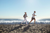 Couple jogging on beach - Stock Image - DT6600