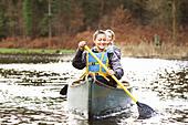 Women rowing canoe on still lake - Stock Image - CT1F6Y