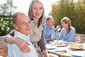 Portrait of senior couple enjoying lunch at table in sunny garden with friends - Stock Image - CC9JMJ