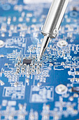 Microcircuit being fixed with soldering iron - sharp photo - Stock Image - D5NNF1