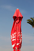 Coca Cola beach umbrella with palm frond. - Stock Image - E46DA3