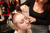 A young woman having a hair and make up beauty make-over in a salon, bleaching her eyebrows, UK - Stock Image - CPY9ME