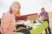 Women preparing lunch in sunny crop field - Stock Image - E89GW2