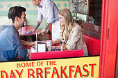 View through window of couple having coffee at diner - Stock Image - DA4WJ2