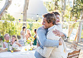 Bridegroom and best man embracing during wedding reception in domestic garden - Stock Image - EHRPJN