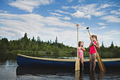 Two young sisters chatting next to canoe on Indian river, Ontario, Canada - Stock Image - E70531