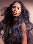 Ethnic beauty portrait of a young woman with beautiful long wavy dark hair - Stock Image - CMP5J1