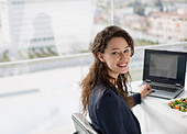 Portrait of smiling businesswoman using laptop and eating lunch - Stock Image - D2XHWN