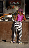 Woman with bandana and black & white striped spandex pants shakes her behind at street bar, Havana, Cuba. - Stock Image - AR2PC5