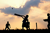 Silhouette of young Indian boys playing cricket against a cloudy sunset background - Stock Image - C82WW7