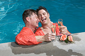 Fully clothed gay couple drinking champagne in swimming pool - Stock Image - AM7M9K
