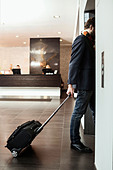 Businessman with luggage entering elevator in hotel - Stock Image - E089F2