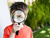 Caucasian boy looking through magnifying glass - Stock Image - C6CTPH
