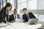 Business people reviewing blueprints at desk - Stock Image - DXPK8C