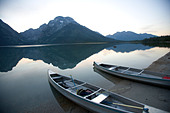 Two canoes at dusk are beached on the shore of Lake Leigh with the Grand Tetons in the distance. - Stock Image - C14RN2