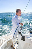 Mature man standing at helm of yacht out at sea, steering, smiling, side view - Stock Image - AHYPJM