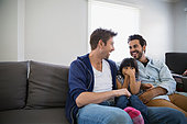 Affectionate homosexual couple and daughter on sofa - Stock Image - ERBP8G