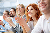 Photo of happy business people applauding at conference, focus on smiling girl - Stock Image - E1D395