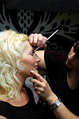 Makeup artist applying makeup to a models face - Stock Image - B17DAW