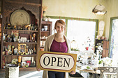 A woman standing in an antique store holding an OPEN sign Displays of goods all around her - Stock Image - DT1J63