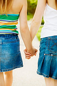 Rear view of girls holding hands - Stock Image - AJPNNG