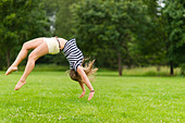Young sporty girl jump backwards at the park, image with narrow depth of field - Stock Image - CYNMC7