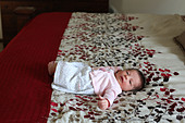 A tiny newborn baby lying on a large bed. - Stock Image - D4AG3C