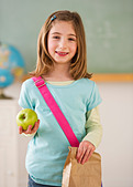 Student in classroom holding lunch - Stock Image - BMJ4C7