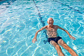 A happy retired man swims in an outdoor pool in the sun enjoying her exercise and keeping fit in her retirement, he treads water - Stock Image - CXPMJ9