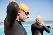 Triathlete tying on goggles outdoors - Stock Image - D7YDXN