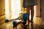 Girl aged four carries toy doll in hall - Stock Image - B0KMJC