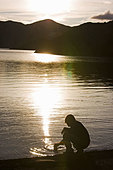Man dipping into still lake - Stock Image - CNKTDT
