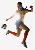 Mixed race soccer player kicking soccer ball in mid-air - Stock Image - BF4NW6