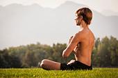 Man meditating in park - Stock Image - D2AT8M
