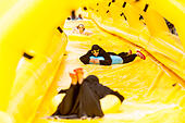 London, UK. 19 June 2015. Girls wearing a traditional chador enjoy the ride, as Lipton promotes its ice tea with a free 100m water slide for members of the public to enjoy for two days at King's Boulevard, King's Cross. © Stephen Chung / Alamy Live News - Stock Image - EW7XBK