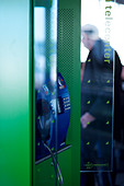 Telephone box in International airport with man in the distance - Stock Image - D110J1
