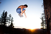 A professional slackliner plays around on the slackline in a field at sunset in the Blue Mountain of Missoula, Montana. - Stock Image - BNRWNY