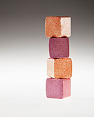 Close up of stacked gold and pink eyeshadow cubes - Stock Image - D2XJ49