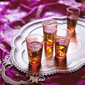 Middle eastern small glasses with mint tea on a tray - Stock Image - AE6WK3