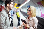 Business people talking in subway station - Stock Image - EF7HCN