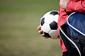 close-up of a young man carrying a football and a sports bag - Stock Image - C49AK8